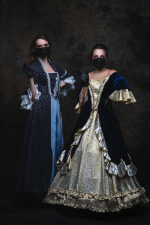 Two women in renaissance dress, face mask and gloves on abstract dark background