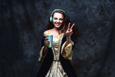 Happy beautiful woman in renaissance dress listens to music in wireless headphones on abstract dark background, old and new concept