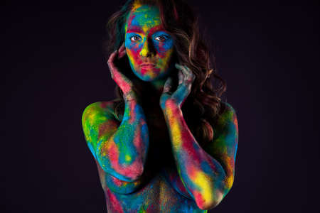 Creative makeup, bright colorful body art on black background, woman painted with powder paints, studio shot