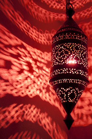 Moroccan lantern lamp with red reflected light with  Swirling lighted patterns on wall photo