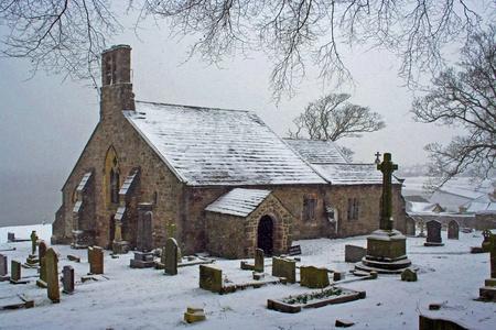 churchyard: village church in the snow