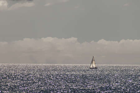 sailboat sails on the open sea under full sail with a sky full of clouds in the background and silver reflections on the sea