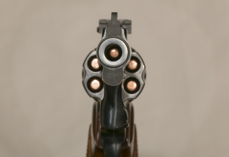 38: A muzzle on view of a loaded blue steel .38 caliber revolver