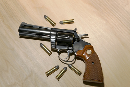 38: A classic blue steel .38 special revolver with spare ammunition