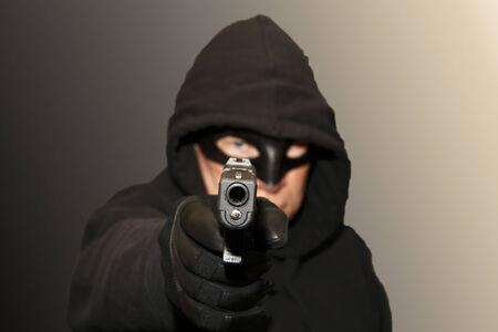 villain: A masked man with a gun.  Is he a villain or hero?  Vigilante or criminal?