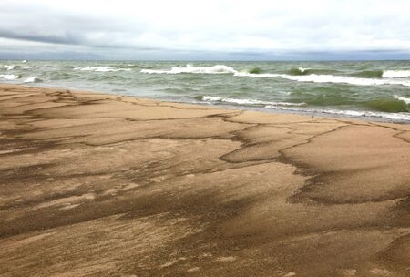 Dramatic sediment patterns left on the beach of Lake Michigan by receding waves in late autumn