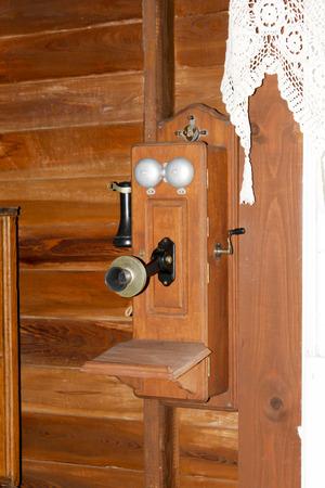 A vintage, wooden crank style telephone photo