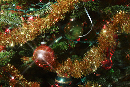 christmas ornamentation: A close up of lights, garland and ornaments with star effects on a live Christmas tree Stock Photo