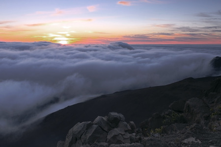 dormant: Sunrise above the clouds at the summit of the dormant volcano Haleakala on Maui, Hawaii