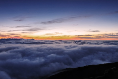 dormant: The first rays of light above the clouds, and moments before sunrise at the summit of the dormant volcano Haleakala on Maui, Hawaii
