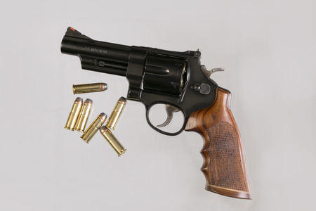 An iconic revolver in 44 Magnum, on a soft white background with extra ammunition photo