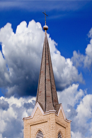 A metal cross adorns a weathered steeple atop and old Catholic church, against a cloudy blue sky photo