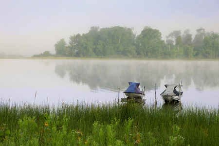 idle: A pair of jet skis sit idle in the fog of a cool early morning on an inland lake