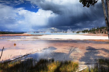prismatic: A rain shower approaches a distant Grand Prismatic Spring in Yellowstone National Park
