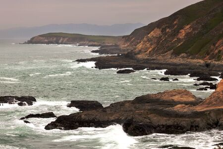 Waves from the Pacific crash against a misty Bodega Head in the light of late evening.  In Bodega Bay, California