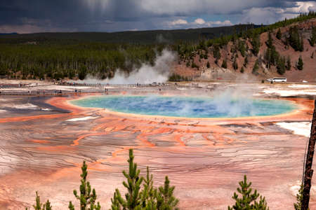 With rain approaching, tourists surround the colorful Grand Prismatic Spring in the Geyser Basin area of Yellowstone National Park, Wyoming 写真素材