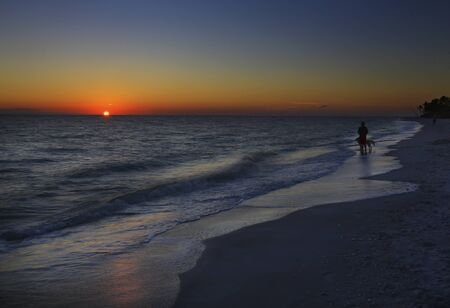 A man with his faithful canine companion taking in a beautiful ocean sunset on Sanibel Island, Florida