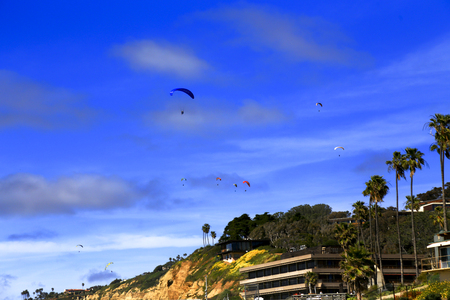Colorful parachute gliders soar gracefully over the cliffs of La Jolla Shores, San Diego, California 報道画像