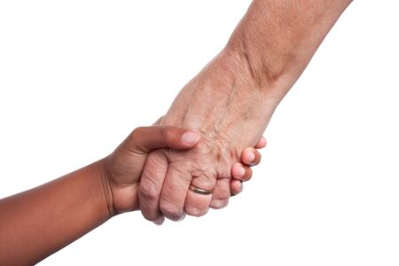 hands out: Young dark skinned mixed race girls hand, holding older senior womans hand