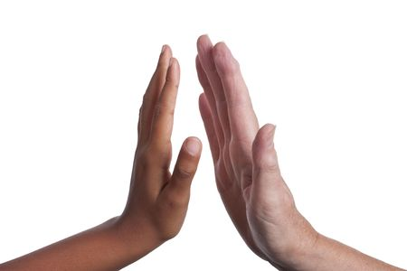 Young dark skinned mixed race girls hand, giving a High Five to an  older fair skinned senior woman's hand.  Stock Photo - 5506390