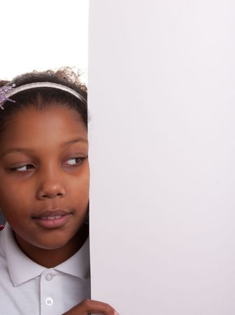 adorable mixed race little girl peeping around edge of sign Stock Photo - 5527261