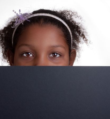 Adorable mixed race little girl peeping over edge of  black sign  photo