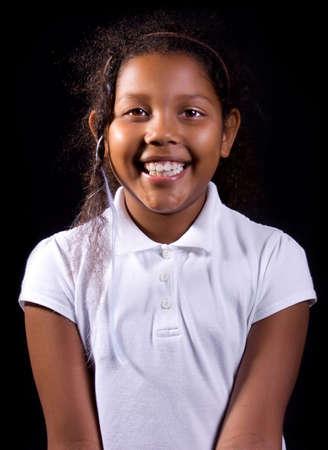 dark skin: Ritratto di razza mista felice africana bambina europea con la pelle scura e nastri in capelli qui, isolata su sfondo nero.
