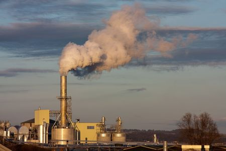 Industrial plant set in rural area spewing out big clouds of steam or smoke pollution under a stting sun. photo