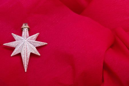 Silver Christmas star decoration on red crepe paper background photo
