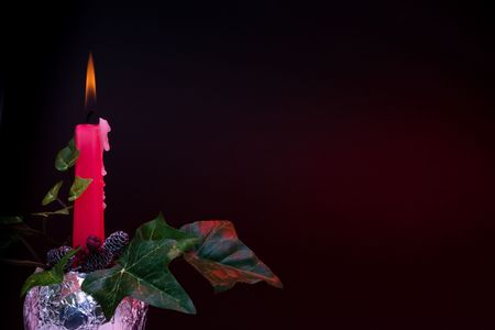 Christmas candle decoration with ivy pine cones and berries photo