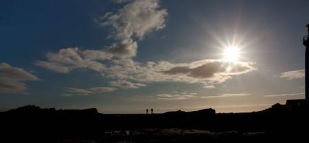 dumfries and galloway: Silhouette of couple on rocks next to Southerness Point Lighthouse, Solway Firth, Dumfries and Galloway,South West Coast of Scotland. Stock Photo