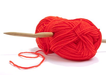 Large ball of red wool or yarn pierced with large wooden knitting needles against white background. photo