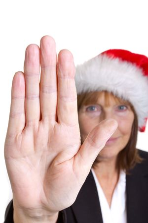 Older senior business womans arthritic hand with knobbly fingers in a stop talk to the hand gesture. Wearing a santa hat. photo
