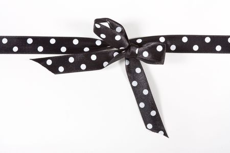 Black and white Polka Dot Ribbon tied in a bow over white card used to wrap up a xmas, birthday or valentine present etc...