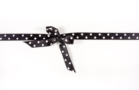 Black and white Polka Dot Ribbon tied in a bow over white card used to wrap up a xmas, birthday  or valentine present etc... Stock Photo