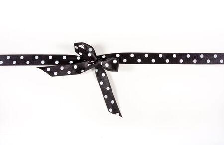 ruban noir: Noir et blanc Polka Dot ruban li� dans un salut sur carte blanche utilis�e pour emmitoufler un etc. pr�sente No�l, anniversaire ou valentine...