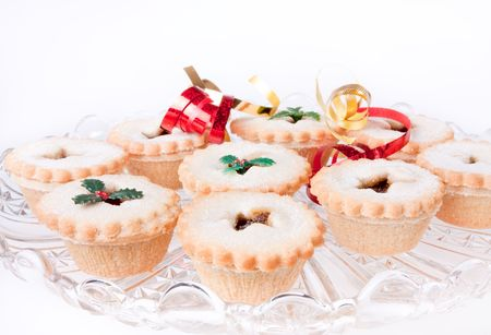 Glass plate of Sweet Mince Pies decorated with ribbons and fake holly. photo