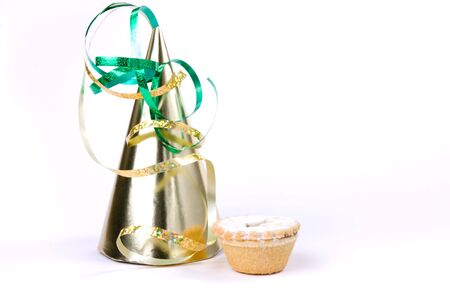 convey: Cone shaped party hat and sweet mince tart isolated against white to convey party food concept.