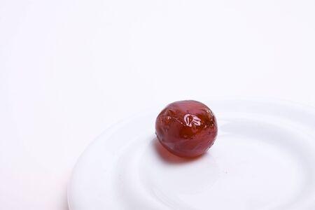 pitted: Una snocciolato scura lucida Morello Glace ciliegina sulla piastra bianca su sfondo bianco.