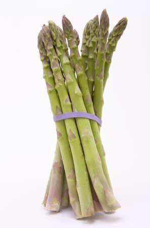 jaunty: Esp�rragos lanzas con bandas de goma color p�rpuras mantenerlos juntos en un �ngulo jaunty aislado contra blanco.  Foto de archivo