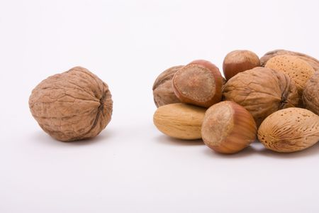 excluded: Festive Mixed Nuts of hazelnuts, walnuts and almonds isolated against white background with excluded lonely walnut. Stock Photo