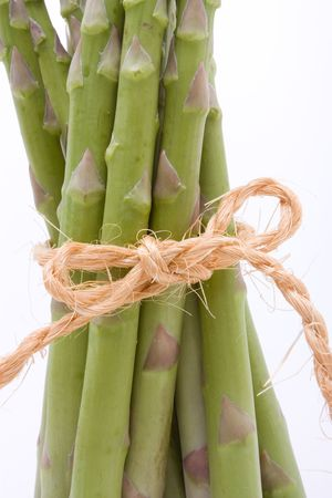 Asparagus spears tied with hemp or sisal string keeping them tidy isolated against white. photo