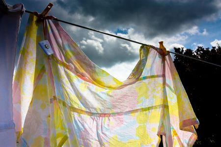 Laundry hanging on washing line in sun with storm approaching about to ruin the  work done concept. photo