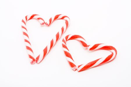 convey: Candy canes arranged in a heart shape against white background to convey valentine concept. Stock Photo