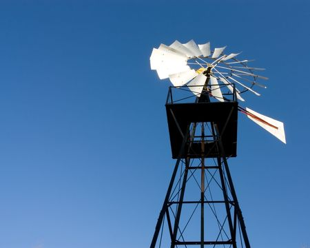 Towering vaned Wind Pump set against vivid blue sky. photo