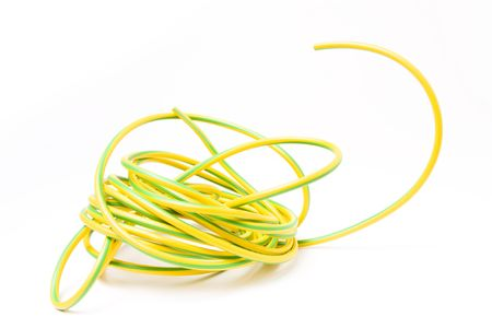 earthing: European yellow and green striped earth wire shielding insulation against white background. Stock Photo