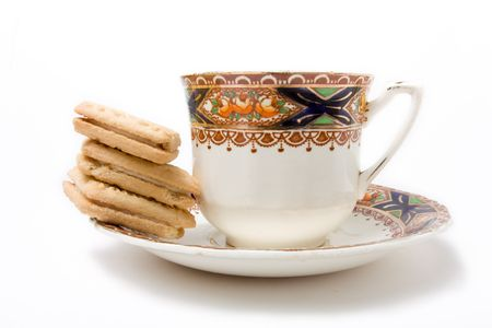 afternoon tea: Tea cup and saucer with stack of custard cream biscuits isolated against white background. Stock Photo
