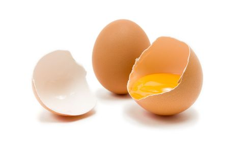 Single whole Hens Egg with cracked egg showing yolk isolated against white background photo