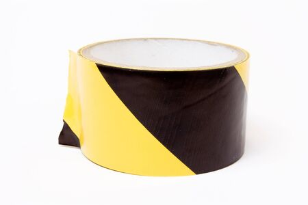 adhesive tape: Roll of yellow and black high visibility tape isolated against white background. Stock Photo