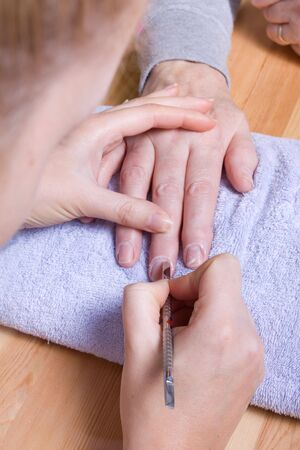 arthritic: Older senior woman with arthritic hands receiving home spa treatment  manicure. Stock Photo
